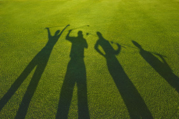 Four golfers with open hands silhouette on grass
