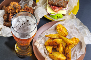 Glass of beer, fries, sandwich and chicken legs