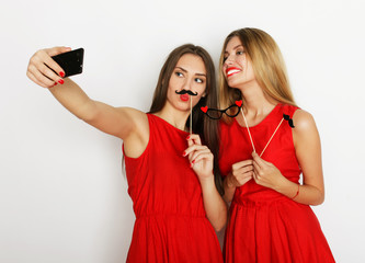two young women wearing red dress taking selfie