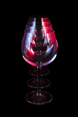 Party wine glasses in nightclub lit by red, blue, lilac lights, nightlife and entertainment industry, objects in row isolated on black background