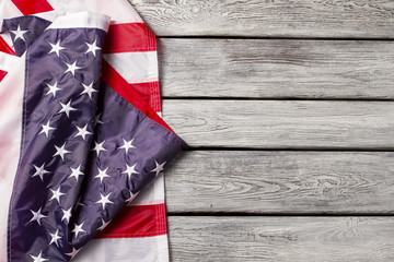Creased national flag of USA. Bright flag on wooden background. Unity means strength. Honor and patriotism.