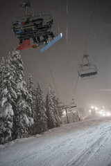 Snowboarders on a Chairlift During a Bright Night of Boarding at the Local Ski Resort.