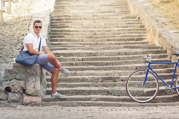 Handsome young man is sitting on the stairs of a fortress while his bicycle is beside him