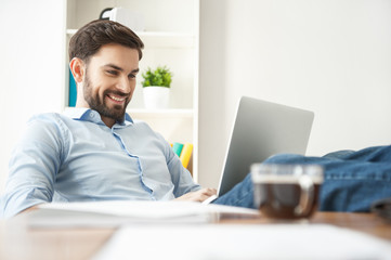 Attractive male freelancer is working on computer