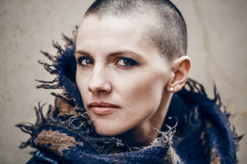 Closeup portrait of sad beautiful Caucasian white young bald girl woman with shaved hair head in leather jacket and scarf shawl, spiritual mood state of mind