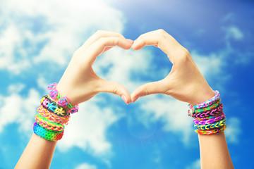 Female hands in shape of heart, on blue sky background