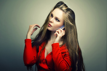 Beautiful young woman in red dress with perfect cute face talking on smartphone. Studio fashion portrait.