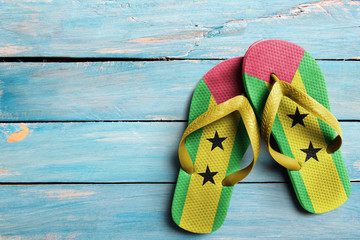 Thongs with flag of Sao Tome, on blue wooden boards