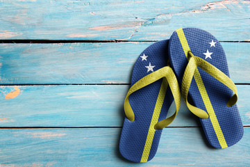 Thongs with flag of Curacao, on blue wooden boards Wall mural