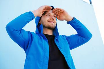 Positive man in blue hoodie looking up.