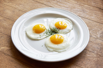 Fried eggs in plate on table