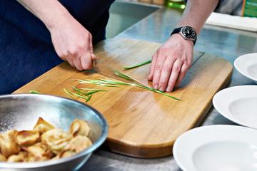Cook cuts green onions for serving dumplings