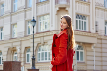 young beautiful woman in red coat in the city