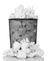 Metal trash can overflowing with paper waste isolated on white.