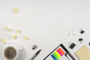 Office table desk with set of colorful supplies, white blank note pad, cup, pen, crumpled paper, flower on white background. Top view and copy space for text