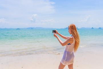 Happy attractive blonde in bikini taking a self picture on a beautiful sunny beach