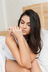 Serious Sexy woman  Sitting at the bed, looking down