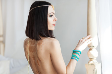 Portrait of attractive young oriental woman in a luxurious gold and turquose jewelry. She has beautiful tanned skin, black hair and bright green eyes. Traditional floral henna drawings on her back.