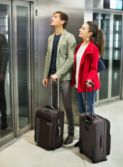 Positive young people with luggage standing