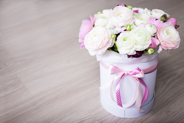 big bouquet of summer flowers in white round box on wooden table