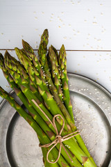 A bunch of asparagus with sesame on a rustic silver plate.