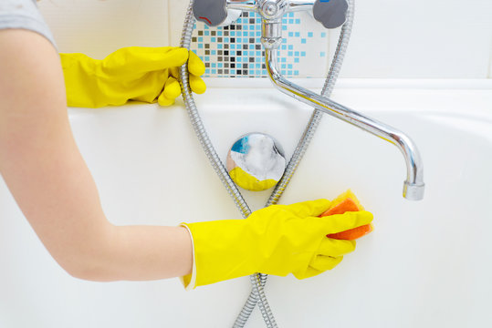 A woman cleaning bath at home. Female washing bathtub and faucet