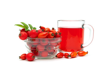 rose hips and hawthorn berries and drink in a cup on a white bac