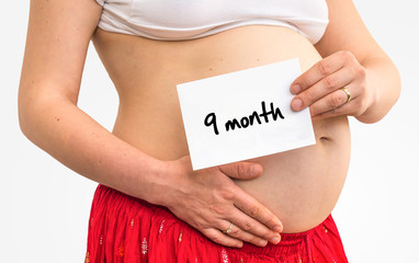 Pregnant woman with inscription: 9 month