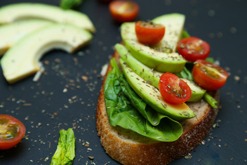 Close up of toast with spinach leaves, avocado and tomatoes.