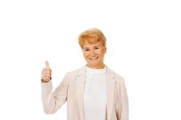 Smile elegant senior woman showing thumb up