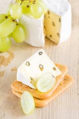 Eine Scheibe Weichkäse mit grünem Pfeffer liegt auf Kräckern. Im Hintergrund liegen ein angeschnittener Weichkäse und Weintrauben.