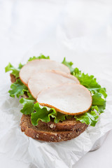 Homemade tasty sandwich with salad leaves and ham on a cutting board on a kitchen background with free space for text, closeup, selective focus