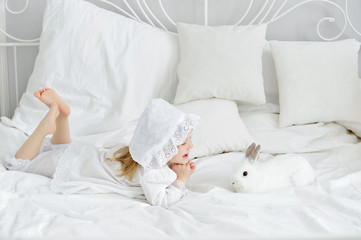 Girl with a rabbit on the bed