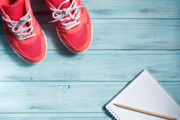 Fitness concept, pink sneakers and notebook with pencil on wooden background, top view