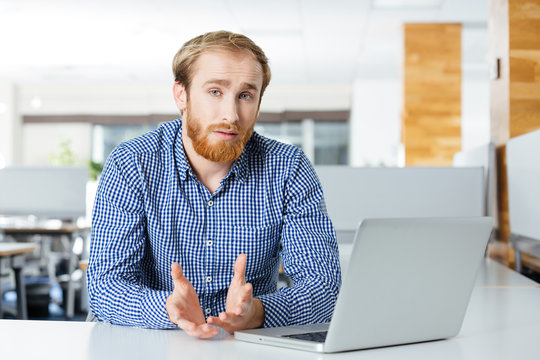 Serious businessman with laptop sitting and talking in office