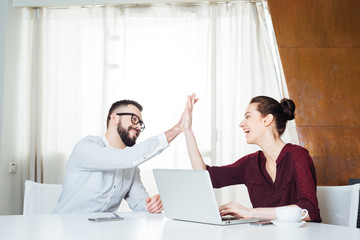 Two cheerful businesspeople celebrating success and giving high five