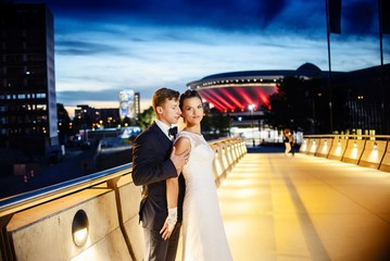 Gorgeous newlyweds on the city bridge at night