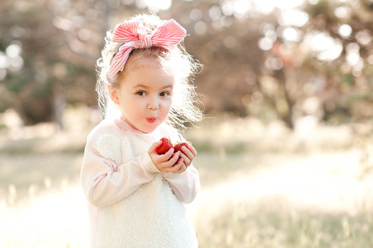Cute kid girl holding strawberries outdoors. Looking at camera. Childhood. Harvesting. Country side.