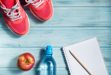 Fitness concept, pink sneakers, red apple, bottle of water and notebook with pencil on wooden background, top view