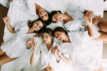 Girls with a bride are lying in the circle