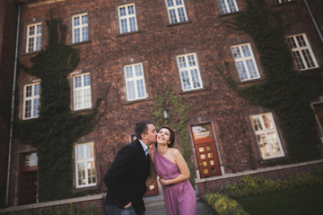 Young wedding couple in love story, bride and groom posing near building on the background. Krakow
