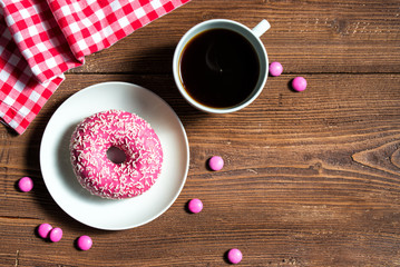 Pink donut on a plate with cup of coffee and pink candies, wooden background, top view