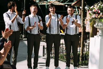 Groomsmen are applauding on the wedding ceremony