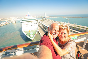 Senior happy couple taking selfie on cruise ship travel at Barcelona harbour - Active retired people having fun