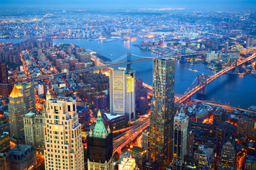 Aerial view of New York City skyline with Three Bridges at dusk