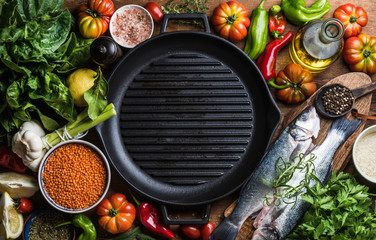 Fototapeta Ingredients for cooking healthy dinner. Raw uncooked seabass fish with vegetables, grains, herbs and spices over rustic wooden background, cast iron pan in center obraz