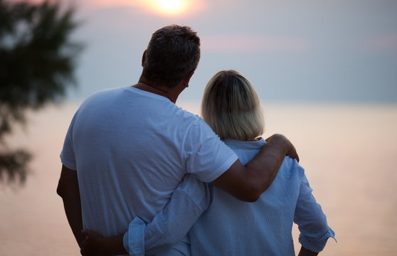 Romantic middle-aged couple standing arm in arm with their backs to the camera enjoying the sunset and a tender moment together