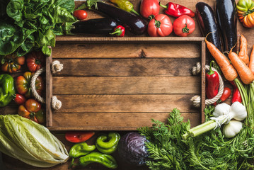 Fresh raw ingredients for healthy cooking or salad making with rustic wooden tray in center, top view, copy space