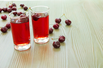 Two glasses of cherry juice and empty space.Left two glasses of cherry juice around scattered cherries, right empty space for text on light green background. Horizontal. Close. Daylight.