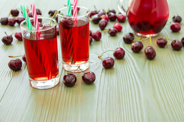 Two glasses of cherry juice and empty space. Left 2 glasses of juice with straws, scattered cherries, jar of cherry juice, on right empty space for text on green background. Horizontal. Daylight.